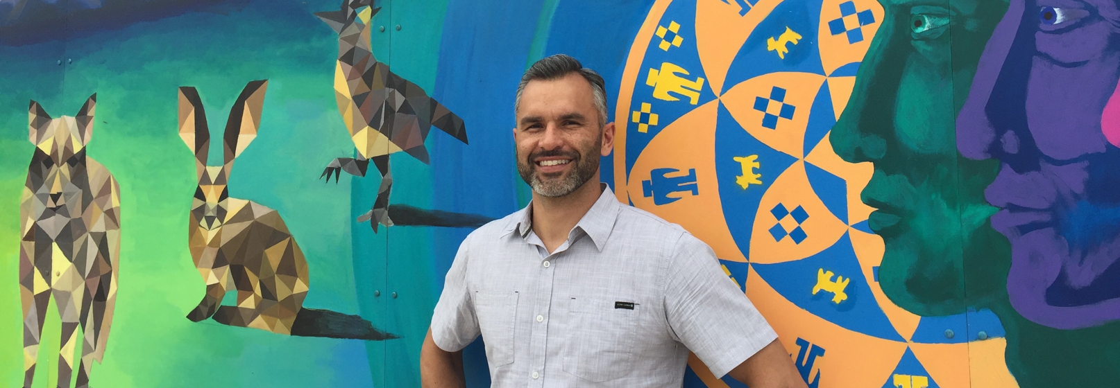 Photograph of Carlos Aguilar in front of a colorful mural